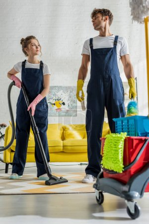 Photo for Selective focus of cleaners in uniform standing near cleaning trolley in modern living room - Royalty Free Image