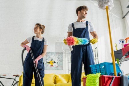 Photo for Selective focus of happy cleaners in uniform looking away near cleaning trolley in modern living room - Royalty Free Image