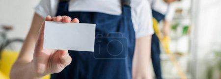 plano panorámico de limpiador en uniforme con tarjeta en blanco