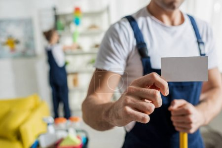 Foto de Vista panorámica del limpiador en una tarjeta en blanco uniforme en el apartamento. - Imagen libre de derechos