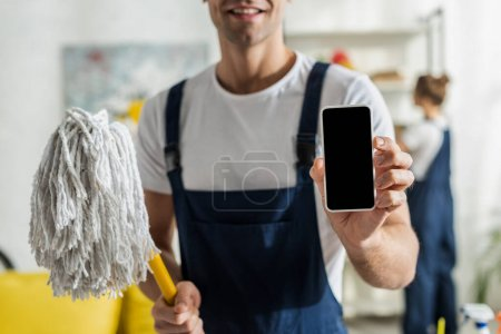 Photo for Cropped view of happy cleaner holding smartphone with blank screen and mop - Royalty Free Image