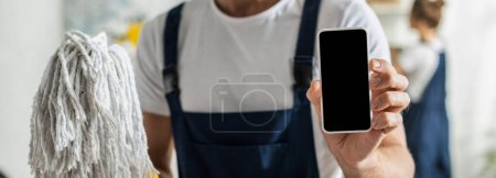 Photo for Panoramic shot of cleaner holding smartphone with blank screen and mop - Royalty Free Image