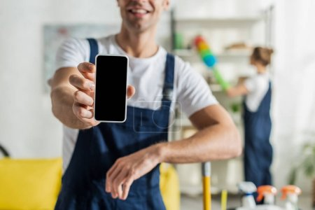 Photo for Cropped view of happy cleaner holding smartphone with blank screen - Royalty Free Image