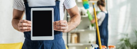 Photo for Panoramic shot of cleaner holding digital tablet with blank screen - Royalty Free Image