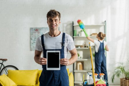 Photo for Selective focus of happy and handsome cleaner holding digital tablet with blank screen - Royalty Free Image