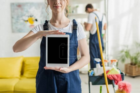 Photo for Cropped view of smiling cleaner holding digital tablet with blank screen - Royalty Free Image