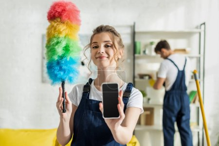 Photo for Selective focus of happy and attractive cleaner holding smartphone with blank screen and duster brush - Royalty Free Image