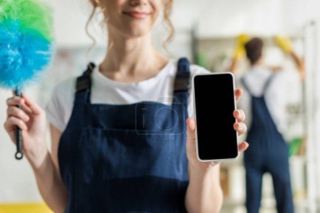 Photo pour Focus view of happy woman in uniform holding smartphone with blank screen and duster brush - image libre de droit