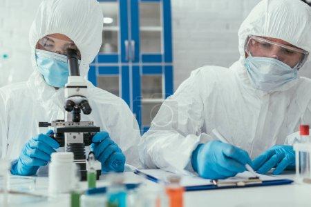 Photo pour Foyer sélectif du biochimiste regardant à travers le microscope près collègue écrire les résultats sur presse-papiers - image libre de droit