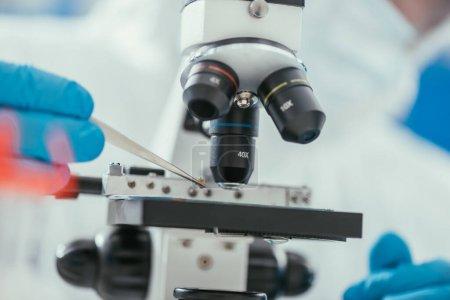 Photo pour Vue partielle du biochimiste tenant une petite pierre avec une pince à épiler près du microscope - image libre de droit