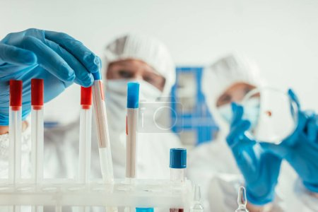 Photo for Selective focus of biochemist taking test tube near colleague holding petri dish - Royalty Free Image
