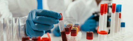 Photo for Cropped view of biochemist taking test tube with blood sample near colleague, panoramic shot - Royalty Free Image