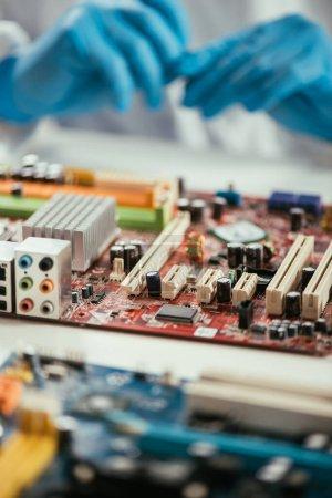 Photo pour Foyer sélectif de la carte mère d'ordinateur près de l'ingénieur dans des gants en caoutchouc - image libre de droit
