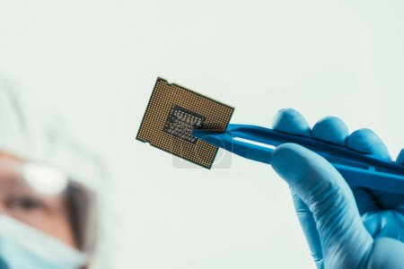 Photo for Cropped view of engineer holding computer microchip with tweezers - Royalty Free Image
