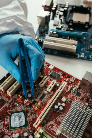 Photo for Cropped view of engineer fixing computer motherboard with tweezers - Royalty Free Image