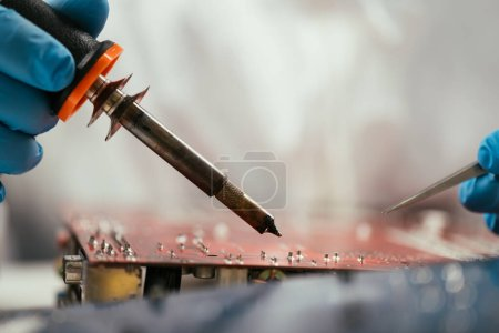 Photo for Cropped view of engineer holding soldering iron near computer motherboard - Royalty Free Image