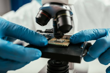 Photo for Cropped view of engineer looking at computer microchip through microscope - Royalty Free Image