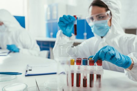 Photo for Biochemist holding test tube with blood sample near colleague in laboratory - Royalty Free Image