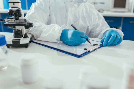 Photo for Cropped view of biochemist writing results on clipboard in laboratory - Royalty Free Image