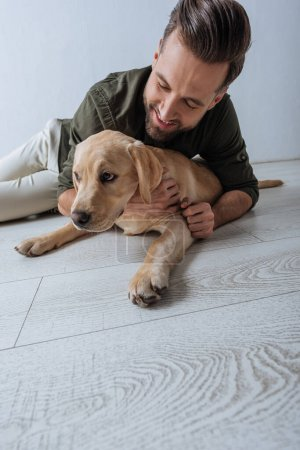 Photo for Low angle view of smiling man petting golden retriever on floor on grey background - Royalty Free Image