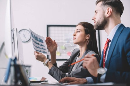 Photo for Side view of data analysts using charts while assessing risk in office - Royalty Free Image