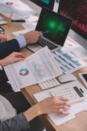 Photo for Cropped view of data analysts using computers, papers with graphs and calculator at table - Royalty Free Image