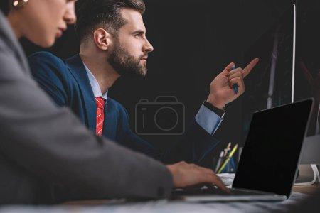 Photo pour Concentration sélective des analystes de la sécurité de l'information travaillant avec un ordinateur portable et des ordinateurs à la table isolé sur noir - image libre de droit