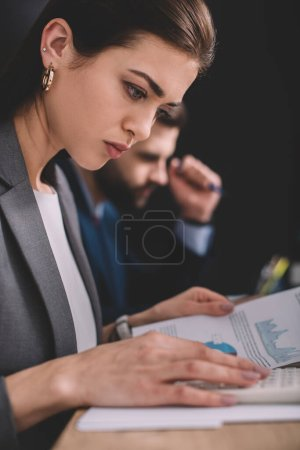 Photo for Selective focus of data analyst working with calculator and charts on paper near colleague on black background - Royalty Free Image