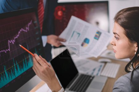 Photo for Selective focus of information security analyst pointing on charts on computer monitor near colleague with papers isolated on grey - Royalty Free Image