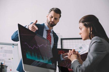 Foto de Enfoque selectivo del analista de datos con documentos que apuntan a los gráficos del monitor de computadora a colega en la oficina. - Imagen libre de derechos