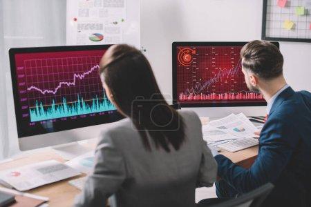 Photo pour Concentration sélective des analystes de la sécurité de l'information travaillant avec des ordinateurs et des documents à la table dans le bureau - image libre de droit