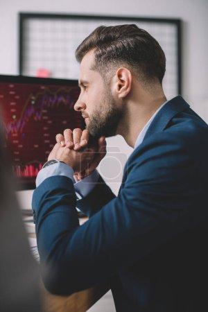 Photo pour Concentration sélective de l'analyste de systèmes informatiques regardant les graphiques sur l'écran d'ordinateur - image libre de droit
