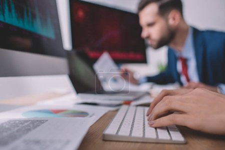 Photo pour Concentration sélective de l'analyste de données tapant sur le clavier de l'ordinateur près de collègue à la table - image libre de droit
