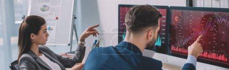 Photo pour Analystes de données pointant sur les graphiques sur les moniteurs d'ordinateur tout en testant le logiciel de sécurité dans le bureau, panoramique - image libre de droit