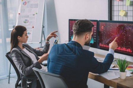 Foto de Los analistas de datos que apuntan a gráficos en monitores de computadoras mientras prueban software de seguridad en la oficina. - Imagen libre de derechos