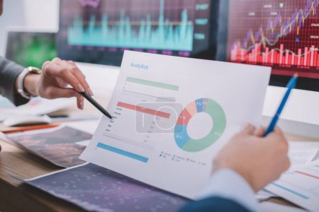 Photo for Cropped view of computer systems analysts working with charts at table - Royalty Free Image