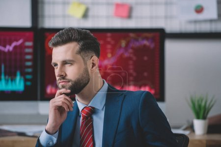 Photo for Pensive computer systems analyst looking away in office - Royalty Free Image
