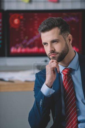 Photo pour Analyste de données confiant avec la main près du menton regardant loin dans le bureau - image libre de droit