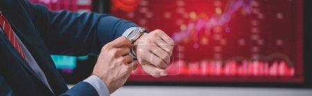 Photo pour Vue recadrée de l'analyste de données vérifiant l'heure sur montre-bracelet, vue panoramique - image libre de droit