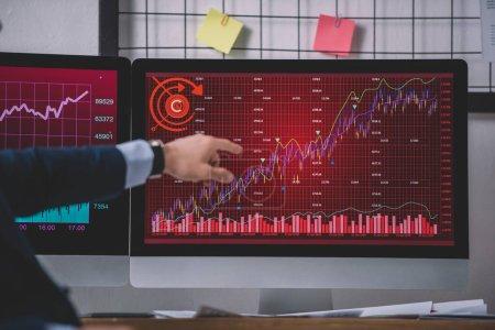 Photo pour Vue recadrée de l'analyste des systèmes informatiques pointant du doigt les graphiques sur l'écran de l'ordinateur - image libre de droit