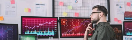 Photo for Side view of pensive data analyst looking away near charts on computer monitors in office, panoramic shot - Royalty Free Image