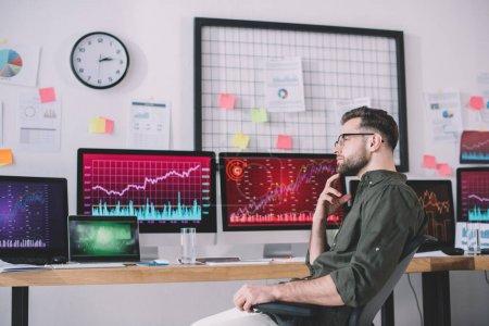 Photo pour Vue latérale d'analyste de données onéreux regardant loin près des cartes sur les écrans d'ordinateur dans le bureau - image libre de droit
