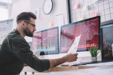Foto de Vista lateral del analista de seguridad de la información sobre gráficos cercanos en monitores de computadoras en la oficina. - Imagen libre de derechos