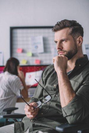 Photo pour Concentration sélective de l'analyste de systèmes informatiques détournant les yeux pendant que le collègue travaille dans le bureau - image libre de droit