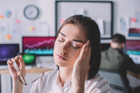 Concentration sélective de l'analyste de données fatigué touchant la tête alors que le collègue travaille au bureau