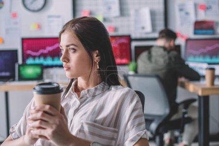 Analista de datos sosteniendo café para llevar mientras su colega trabaja en la oficina