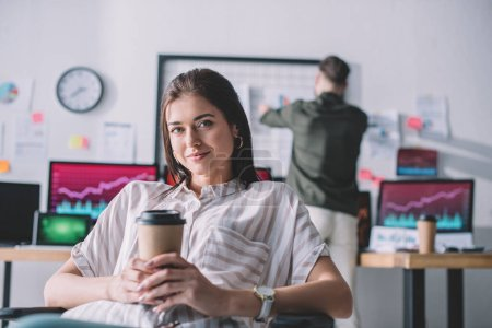 Photo for Smiling data analyst holding coffee to go while colleague working in office - Royalty Free Image