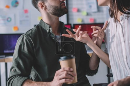 Vue recadrée de l'analyste de données tenant une tasse en papier et parlant à un collègue