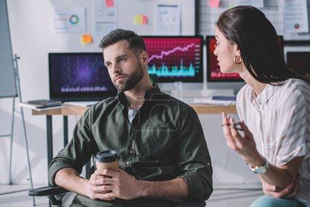 Concentration sélective de l'analyste de la sécurité de l'information parler à un collègue avec du café pour aller au bureau