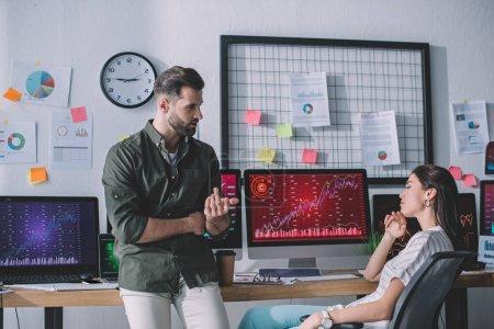 Photo pour Les analystes de systèmes informatiques planifient la stratégie près des cartes sur les écrans d'ordinateur sur la table - image libre de droit